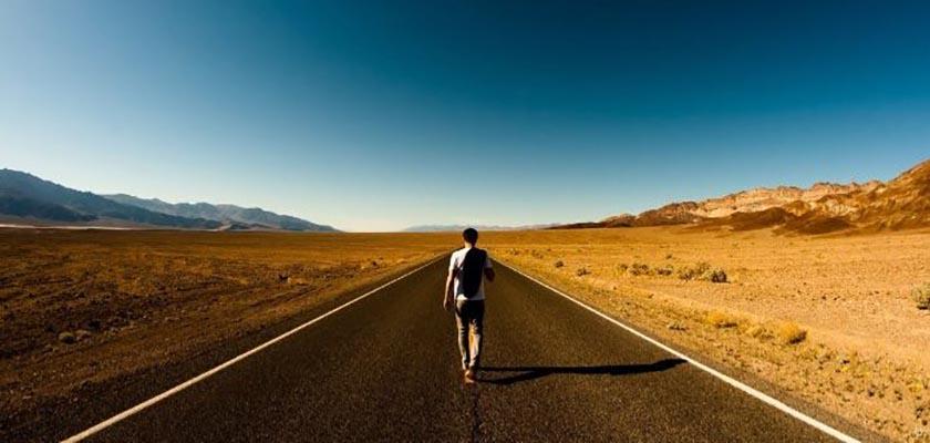 homem caminhando na estrada sozinho
