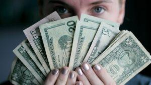 mulher segurando dinheiro